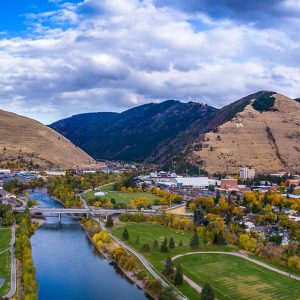 landscape image of river running through Missoula with mountains in background