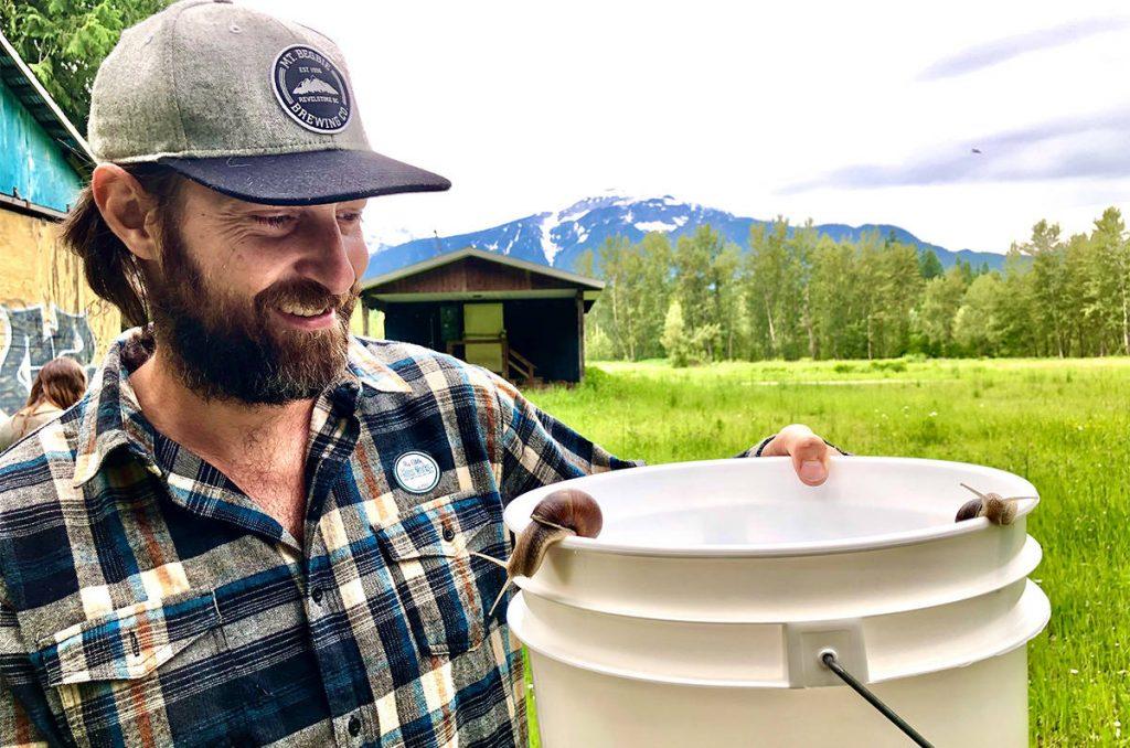 man looks at snail on white bucket